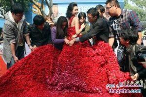 بالصور.. شاب صيني يتقدم لحبيبته بطلب الزواج بفستان من عشرة آلاف وردة حمراء!